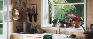 garden window with flowers on the shelf in a kitchen